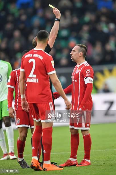 Referee Sascha Stegemann shows Franck Ribery of Bayern Muenchen a yellow card during the Bundesliga match between VfL Wolfsburg and FC Bayern...