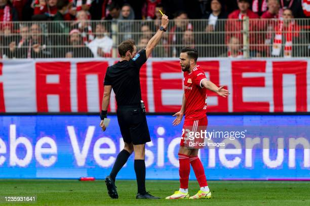 Referee Sascha Stegemann shows Niko Giesselmann of 1. FC Union Berlin the yellow card during the Bundesliga match between 1. FC Union Berlin and VfL...