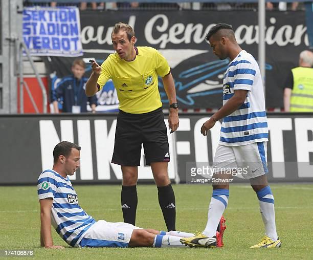 Referee Sascha Stegemann stands close to injured Tanju Oeztuerk of Duisburg and Phil OfosuAyeh during the 3rd league match between MSV Duisburg and 1...