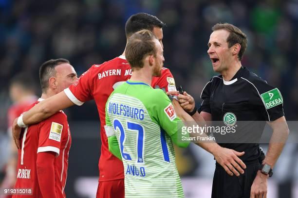 Referee Sascha Stegemann talks with Sandro Wagner of Muenchen and Maximilian Arnold of Wolfsburg during the Bundesliga match between VfL Wolfsburg...