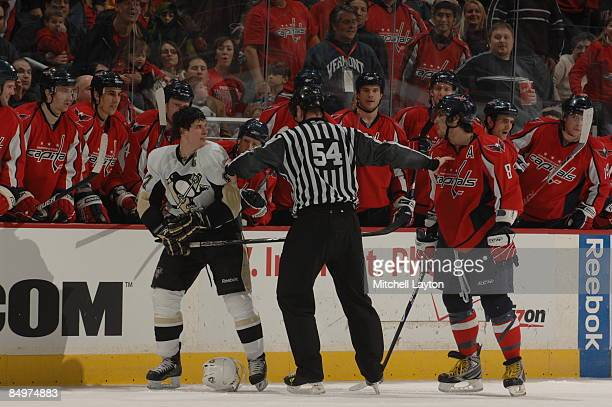 A referee separates Alex Ovechkin of the Washington Capitals and Sidney Crosby of the Pittsburgh Penguins in front of the Washington Capitals bench...