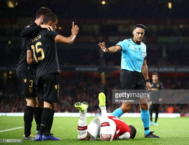 Referee Serdar Gozubuyuk deals with a incident between Alexandre Lacazette of Arsenal and Victor Garcia of Vitoria Guimaraes during the UEFA Europa...