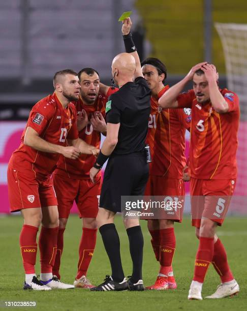 Referee Sergey Karasev shows Goran Pandev of North Macedonia a yellow card during the FIFA World Cup 2022 Qatar qualifying match between Germany and...