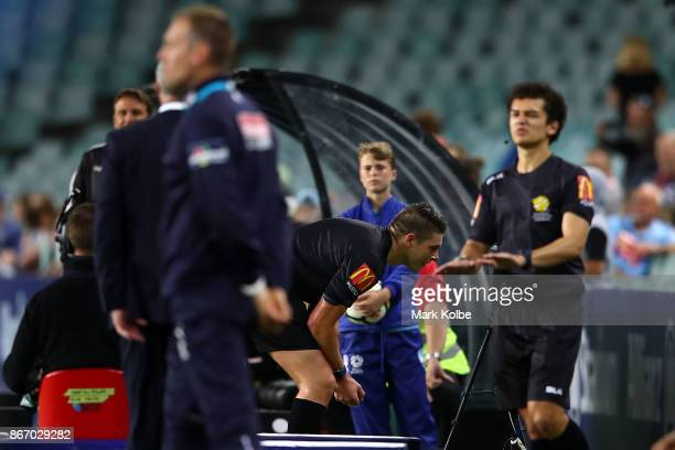 Referee Shaun Evans watches a replay on a screen on the sideline after calling for a referral during the round four ALeague match between Sydney FC...