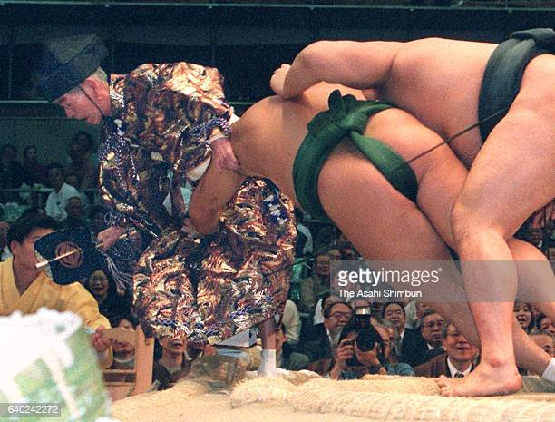Referee Shikimori Inosuke is pushed out during a bout between Mongolian Kyokushuzan and Takanohana during day five of the Grand Sumo Spring...