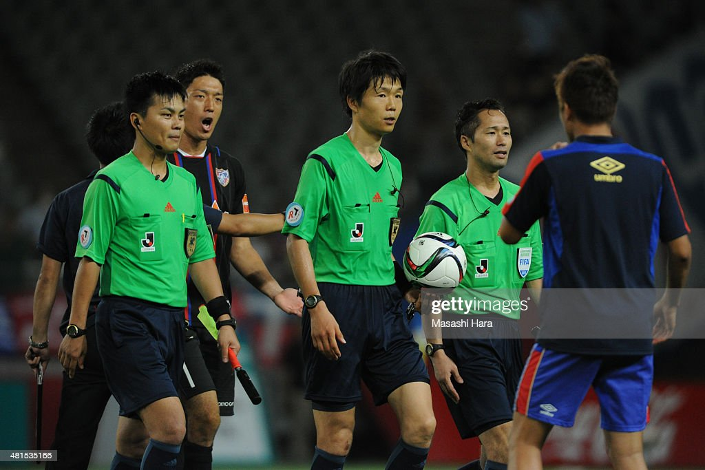 Referee Shoichiro Mikami (C) walks off the pitch during the J.League match between FC Tokyo and Albirex Niigata at Ajinomoto Stadium on July 15, 2015 in Chofu, Tokyo, Japan.