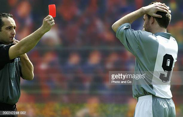 Referee showing football player red card
