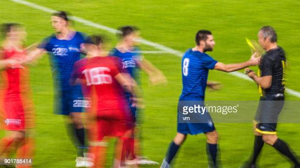 Referee showing yellow card on the field