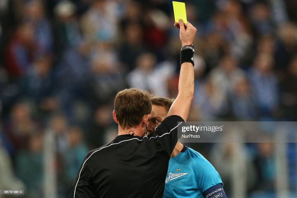 Referee shows the yellow cards to Domenico Criscito during the Russian Football League match between FC Zenit Saint Petersburg and FC Lokomotiv Moskva at Saint Petersburg Stadium on October 29, 2017 in St. Petersburg, Russia.