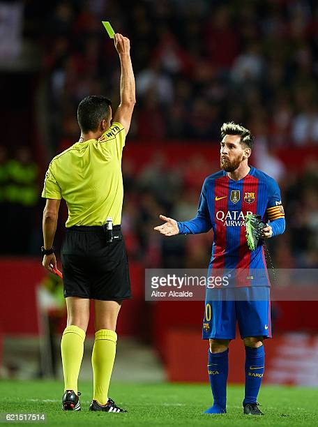 Referee shows yellow card to Lionel Messi of FC Barcelona during the match between Sevilla FC vs FC Barcelona as part of La Liga at Ramon Sanchez...