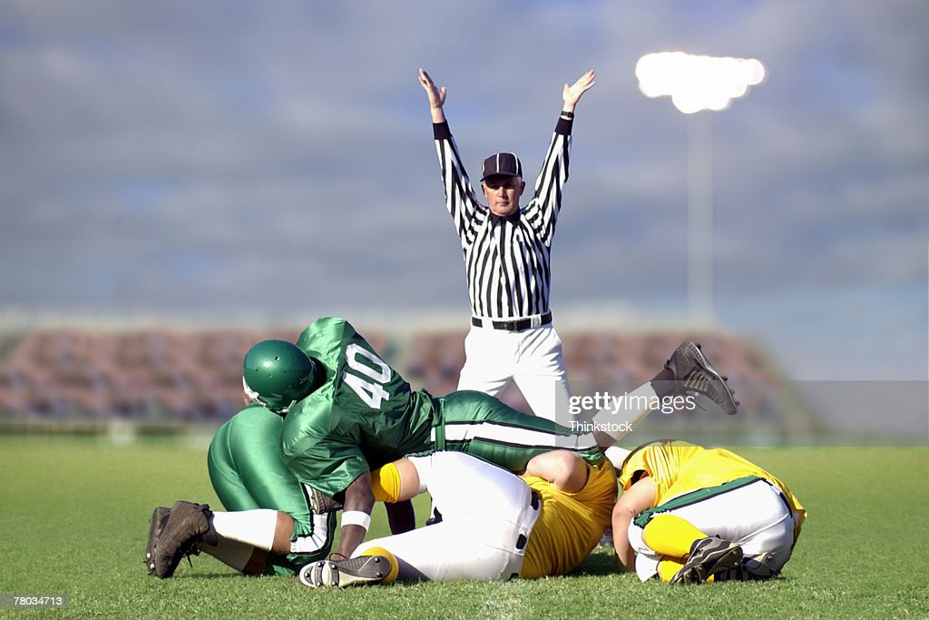 Referee signaling touchdown during football game : Stock Photo
