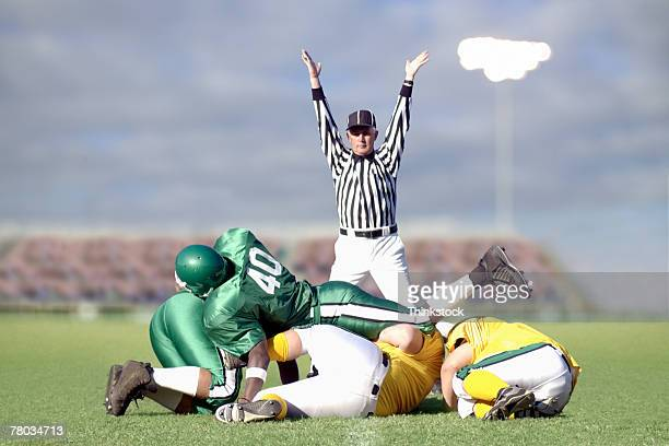 Referee signaling touchdown during football game