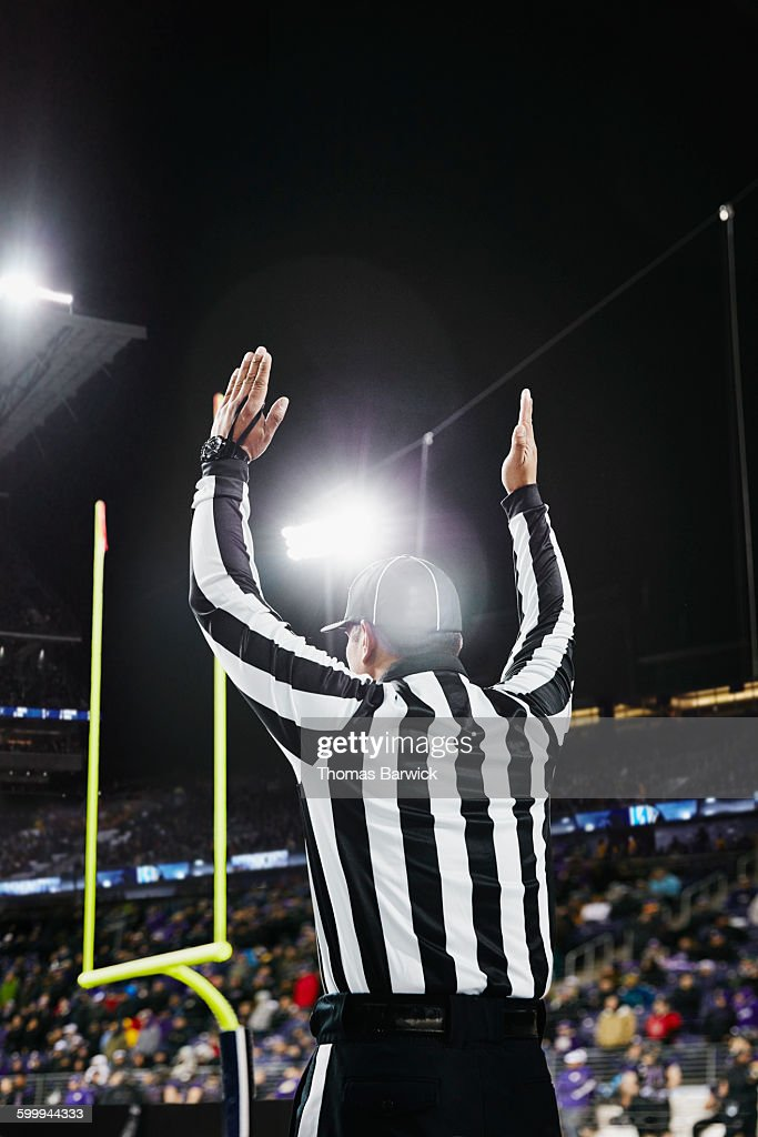 Referee signaling touchdown on field during game : Stock Photo