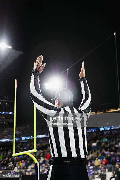 Referee signaling touchdown on field during game
