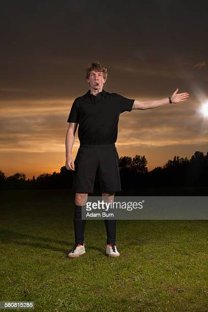 Referee signaling while blowing whistle on soccer field