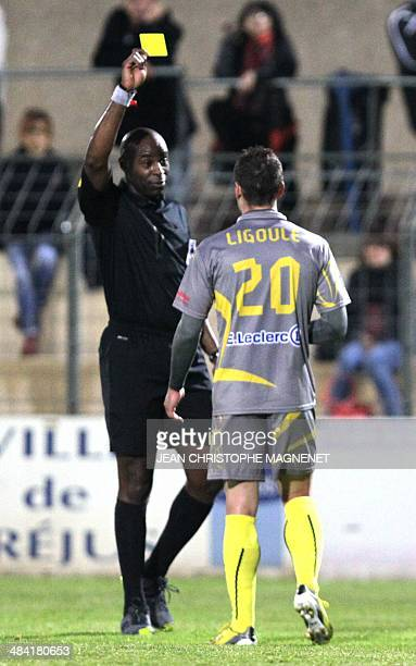 Referee Silas Billong shows the yellow card to US Orleans' French midfielder Matthieu Ligoule during the French National football match between FC...