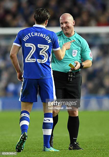 Referee Simon Hooper speaks with Sam Hutchinson of Sheffield Wednesday before showing him a yellow card for a tackle on Connor Ronan of Wolverhampton...