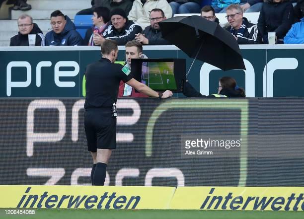 Referee Soeren Storks checks the VAR screen during the Bundesliga match between TSG 1899 Hoffenheim and VfL Wolfsburg at PreZero-Arena on February...