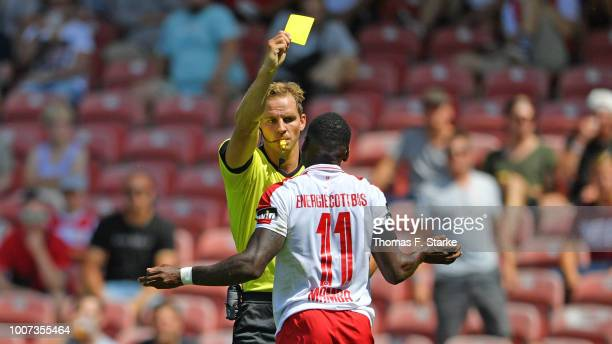 Referee Soeren Storks shows the yellow card to Streli Mamba of Cottbus during the 3. Liga match between FC Energie Cottbus and F.C. Hansa Rostock at...