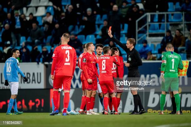 Referee Soeren Storks shows the yellow red card to Elias Huth of Zwickau during the 3. Liga match between Chemnitzer FC and FSV Zwickau at Stadion an...