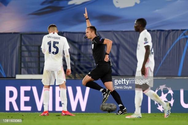 Referee Srdjan Jovanovic rules out a Real Madrid goal after checking VAR during the UEFA Champions League Group B stage match between Real Madrid and...