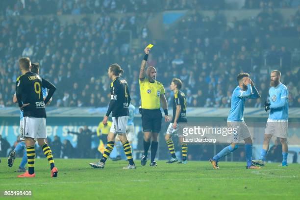Referee Stefan Johanessen give Erdal Rakip of Malmo FF a yellow card during the allsvenskan match between Malmo FF and AIK at Swedbank Stadion on...