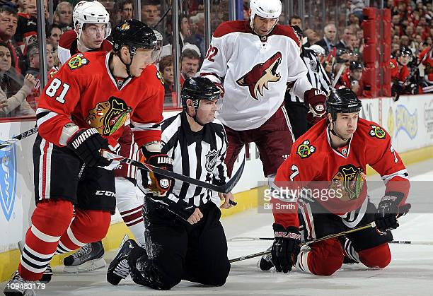 Referee Stephane Auger and Brent Seabrook of the Chicago Blackhawks kneel on the ice as Marian Hossa of Chicago skates forward while Mikkel Boedker...