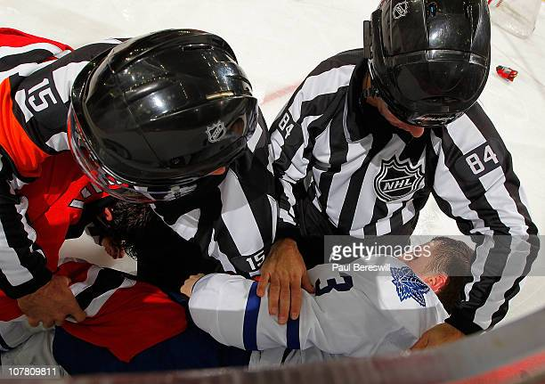 Referee Stephane Auger and linesman Tony Sericolo tend to Dion Phaneuf of the Toronto Maple Leafs during a fight in an NHL hockey game against the...