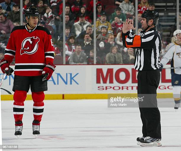 Referee Stephane Auger calls an interference penalty against Dainius Zubrus of the New Jersey Devils during the game against the Nashville Predators...