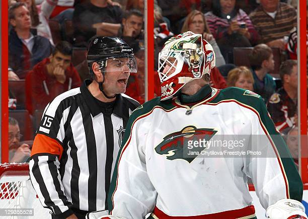 Referee Stephane Auger chats with Niklas Backstrom of the Minnesota Wild in an NHL game against the Ottawa Senators during the NHL home opener to...