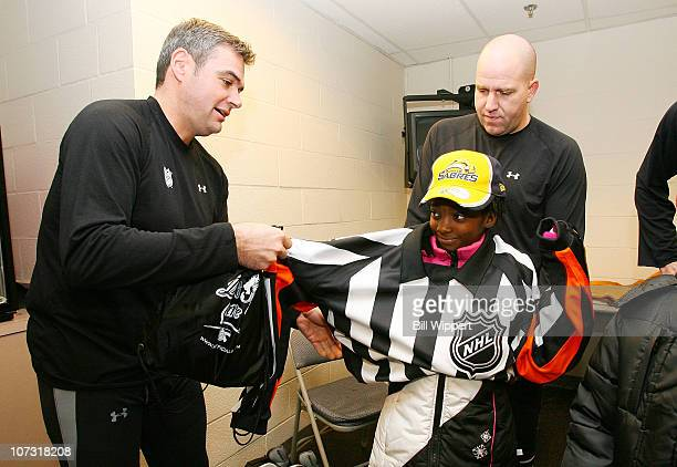 Referee Stephane Auger lets Jayda Soules try on his offical's jersey with the help of linesman Michel Cormier before the game between the Buffalo...