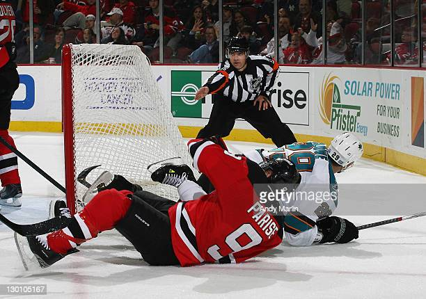 Referee Stephane Auger signifies goal as Zach Parise of the New Jersey Devils and Ryane Clowe of the San Jose Sharks fall to the ice after Clowe's...
