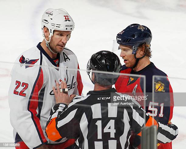 Referee Stephane Auger talks to Mike Knuble of the Washington Capitals and Brian Campbell of the Florida Panthers about a disputed goal by Stephen...
