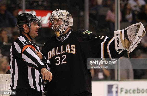NHL referee Stephane Auger talks with Kari Lehtonen of the Dallas Stars at American Airlines Center on November 15 2011 in Dallas Texas