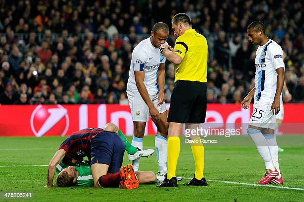 Referee Stephane Lannoy of France shows the yellow card to Cesc Fabregas of Barcelona after he slid in on goalkeeper Joe Hart of Manchester City...