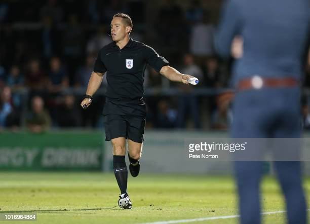 Referee Stephen Martin with a bottle that was thown onto the pitch during the Carabao Cup First Round match between Wycombe Wanderers and Northampton...