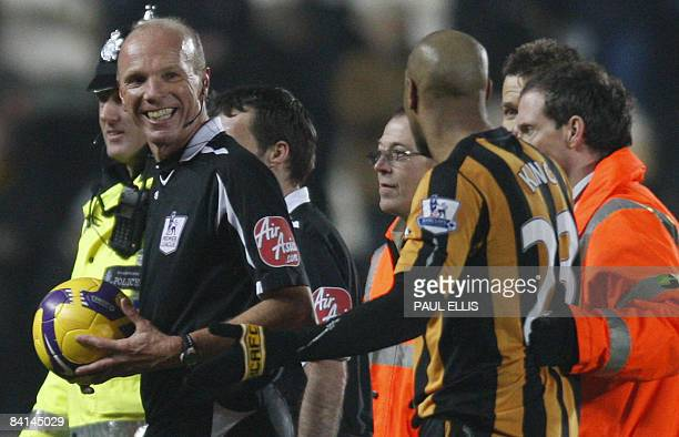 Referee Steve Bennett laughs with Hull City's Jamaican forward Marlon King after the English Premier League football match against Aston Villa at The...