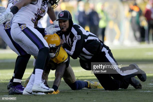 Referee Steve Freeman attempts to break up a fight between Geronimo Allison of the Green Bay Packers and Chuck Clark of the Baltimore Ravens in the...