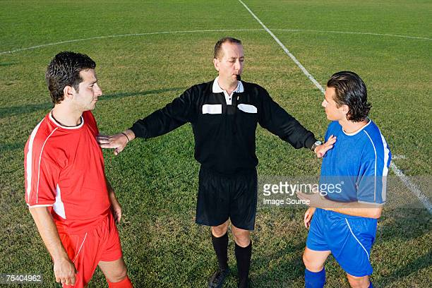 referee stopping two footballers - referee stock photos and pictures