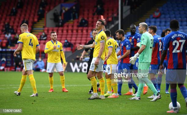 Referee Stuart Attwell awards Lewis Dunk of Brighton and Hove Albion a red card during the Premier League match between Crystal Palace and Brighton &...