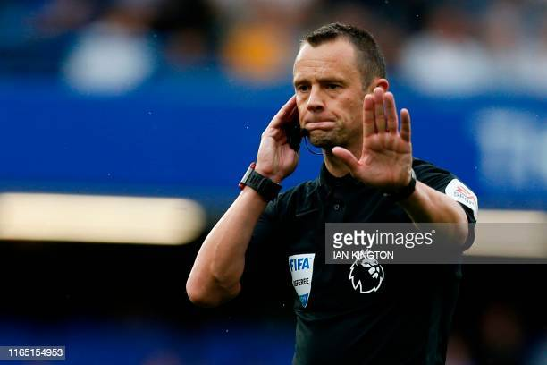 Referee Stuart Attwell checks a decision with the VAR during the English Premier League football match between Chelsea and Sheffield United at...