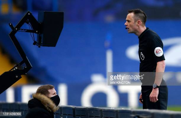 Referee Stuart Attwell checks a screen during a VAR review for a potentional hand-ball incendent during the English Premier League football match...