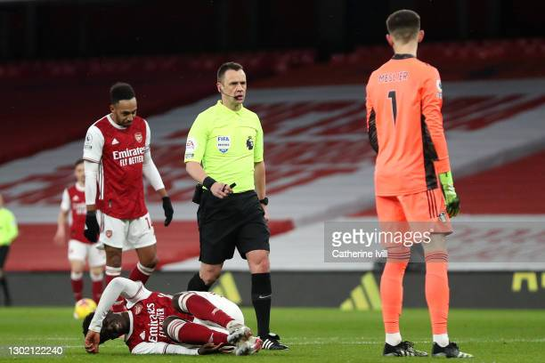 Referee, Stuart Attwell goes over to Illan Meslier of Leeds United after he commits a foul on Bukayo Saka of Arsenal in the penalty box, leading to a...