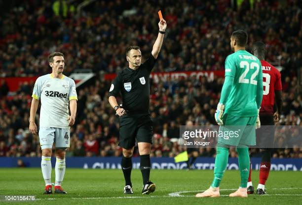 Referee Stuart Attwell shows Sergio Romero of Manchester United a red card for a handball during the Carabao Cup Third Round match between Manchester...