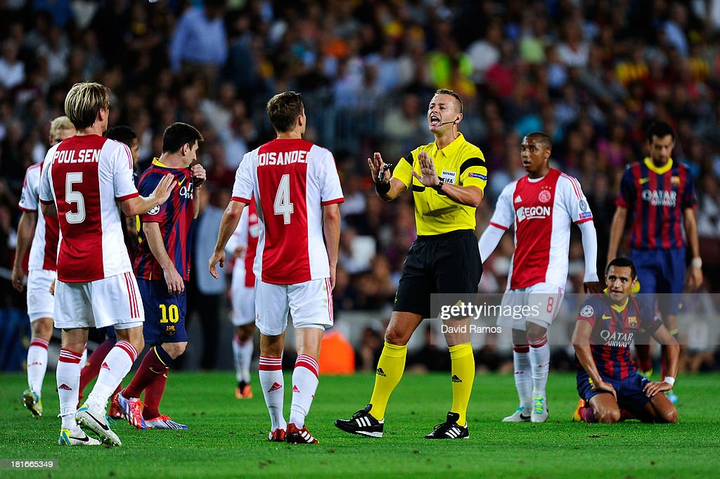Referee Svein Oddvar Moen argues with Ajax Amsterdam players during the UEFA Champions League Group H match between FC Barcelona and Ajax Amsterdam at the Camp Nou stadium on September 18, 2013 in Barcelona, Spain.