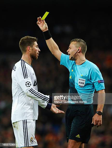 Referee Svein Oddvar Moen shows the yellow card to Sergio Ramos of Real Madrid during the UEFA Champions League Quarter Final first leg match between...