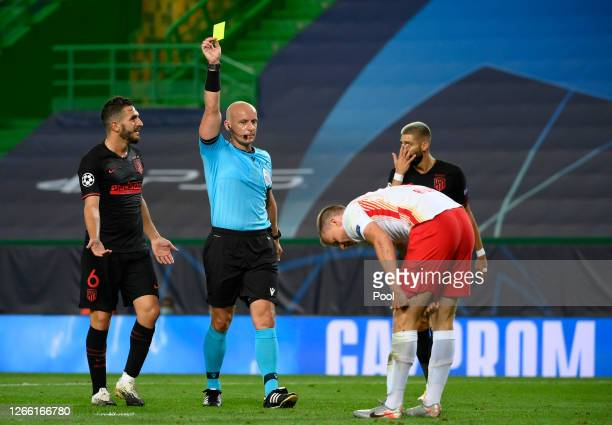 Referee Szymon Marciniak awards Lukas Klostermann of RB Leipzig a yellow card during the UEFA Champions League Quarter Final match between RB Leipzig...