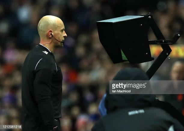 Referee Szymon Marciniak checks the VAR screen during the UEFA Europa League round of 16 first leg match between Rangers FC and Bayer 04 Leverkusen...
