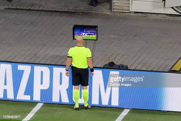 Referee Szymon Marciniak looks on the VAR during the UEFA Champions League Group H stage match between RB Leipzig and Paris Saint-Germain at Red Bull...