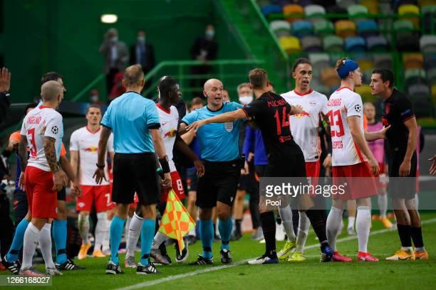 Referee Szymon Marciniak separates Amadou Haidara of RB Leipzig and Marcos Llorente of Atletico de Madrid during the UEFA Champions League Quarter...